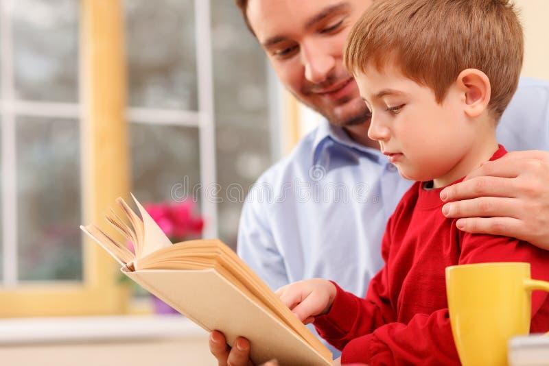 De vrolijke mannelijke ouder onderwijst zijn kind stock afbeelding