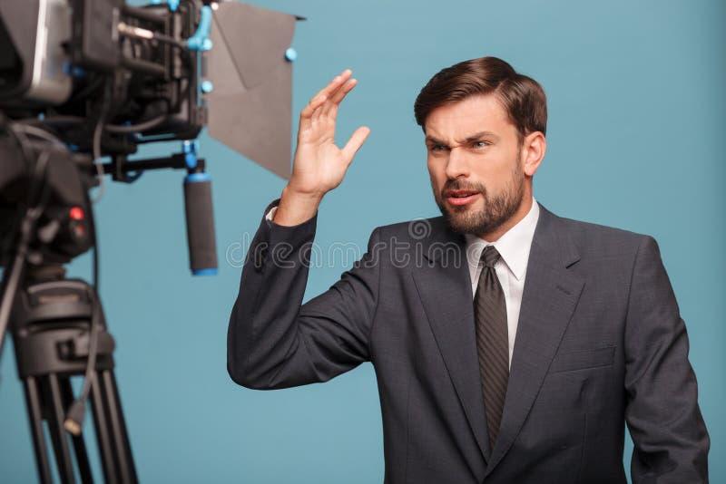 De vrolijke mannelijke verslaggever werkt met stock foto's