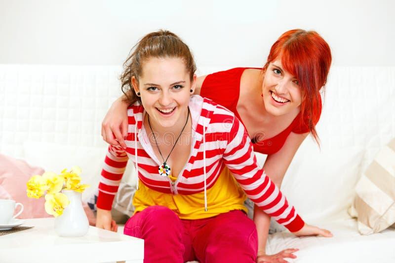De vrolijke meisjes die op bank zitten en hebben pret stock foto's