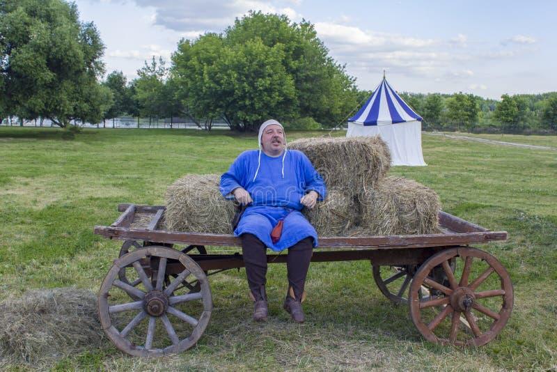 De vrolijke mens in middeleeuwse blauwe kleren zit op een door paarden getrokken kar op de achtergrond van green stock afbeelding