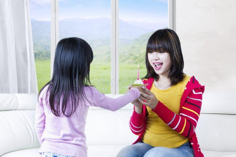 De vrolijke moeder krijgt cupcake stock foto's