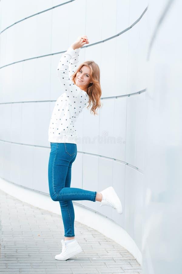 De vrolijke mooie positieve jonge vrouw in modieuze kleren heeft pret binnen op een warme de lentedag dichtbij de moderne muur stock foto