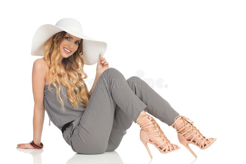 De vrolijke Mooie Vrouw in Jumpsuit, Zonhoed en Hoge Hielen zit op Vloer stock foto's