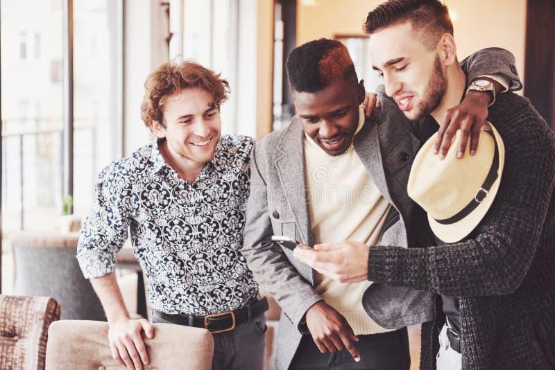 De vrolijke oude vrienden communiceren met elkaar en telefoonhorloge in bar Concept vermaak en levensstijl Wifi stock foto