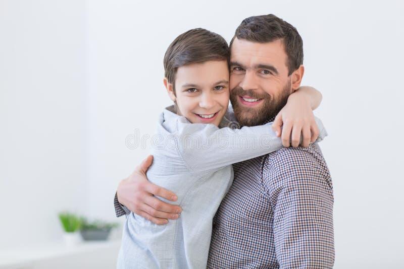 De vrolijke papa en het jonge geitje koesteren mooi stock afbeelding
