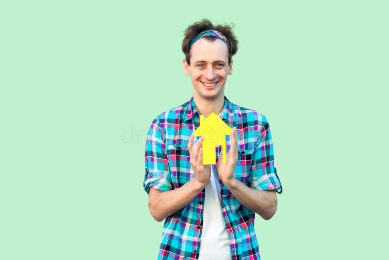 De vrolijke positieve blije optimistische jonge volwassen mens in geruit overhemd heeft droom en holdingsdocument plattelandshuis stock afbeeldingen