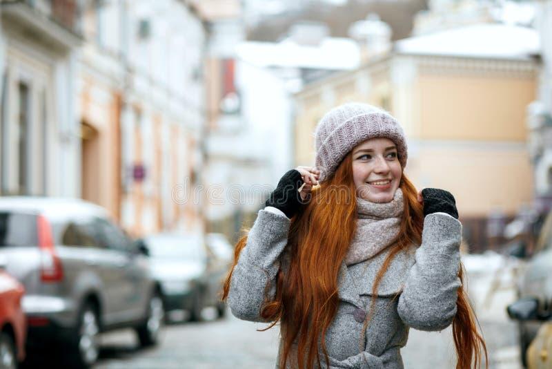 De vrolijke rode haired vrouw die warme de winterkleren dragen die lopen stock foto