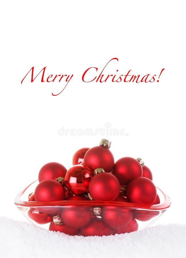 De vrolijke Rode Snuisterijen van Kerstmis in de Kom van het Glas met Sno stock fotografie
