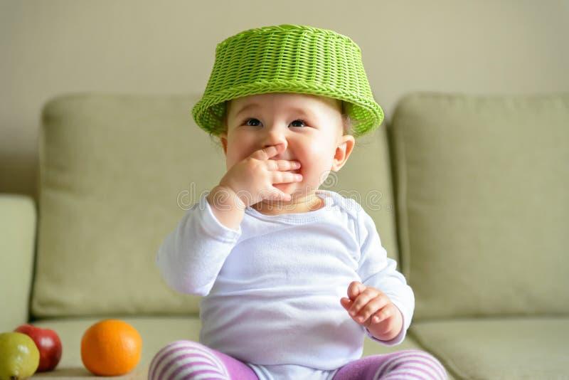 De vrolijke spelen van het babymeisje met schotel en fruit royalty-vrije stock foto