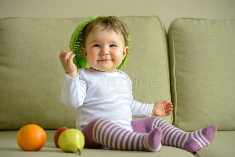 De vrolijke spelen van het babymeisje met schotel en fruit royalty-vrije stock fotografie