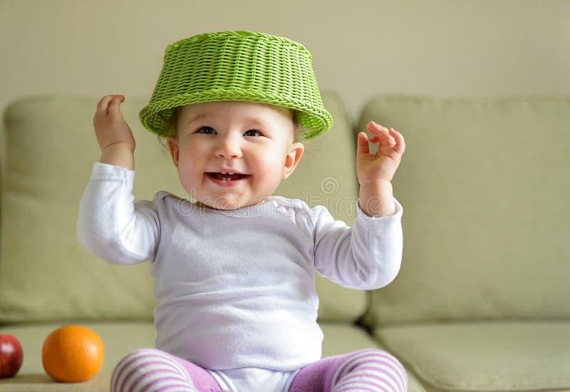 De vrolijke spelen van het babymeisje met schotel en fruit stock afbeelding