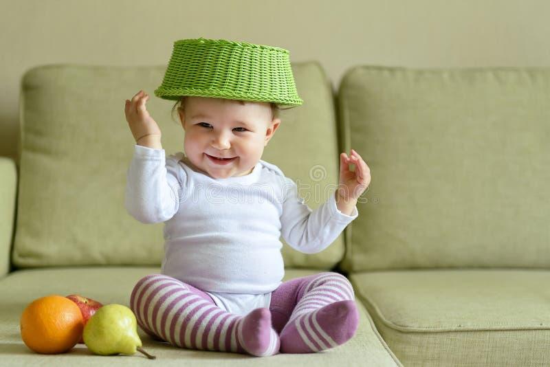 De vrolijke spelen van het babymeisje met schotel en vruchten stock fotografie