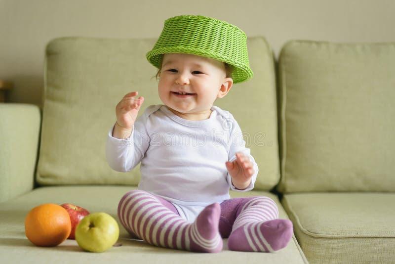 De vrolijke spelen van het babymeisje met vruchten thuis royalty-vrije stock afbeelding