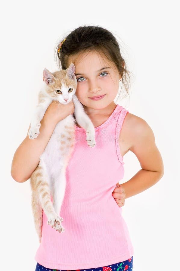 De vrolijke spelen van het kindmeisje met een klein katje op een lichte achtergrond stock fotografie