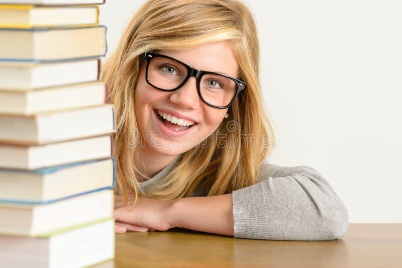 De vrolijke studententiener kijkt van achter boeken royalty-vrije stock afbeeldingen