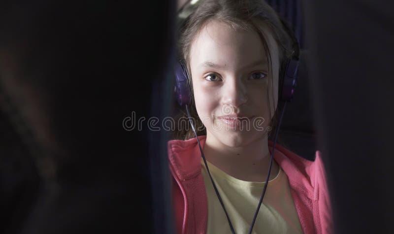 De vrolijke tiener luistert aan muziek op hoofdtelefoons in de cabine van vliegtuig terwijl het reizen royalty-vrije stock foto's