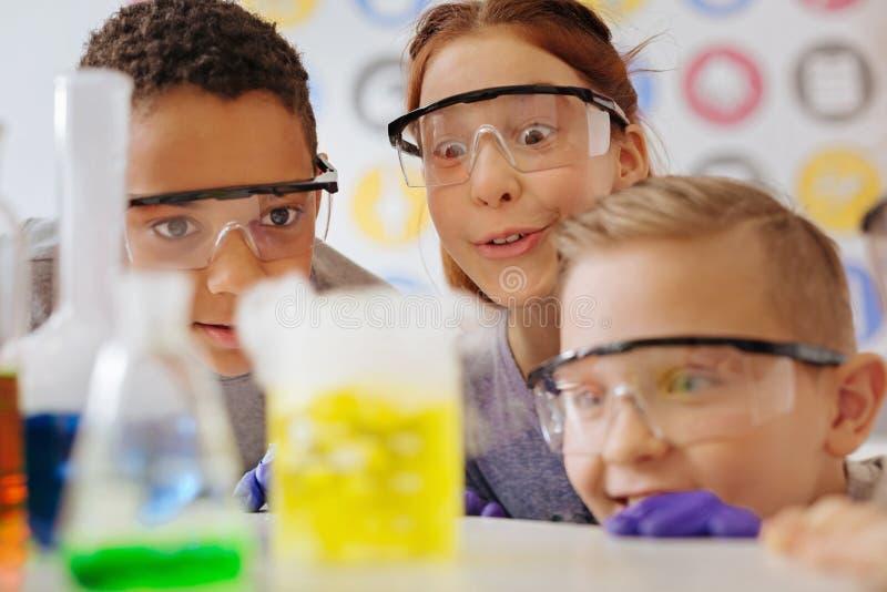 De vrolijke tienerklasgenoten die op chemische substantie letten reageren in fles stock fotografie