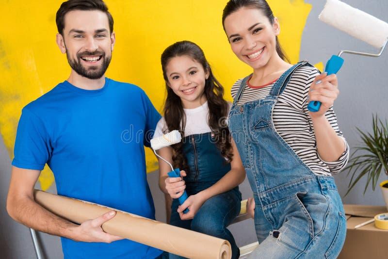 De vrolijke vader, de moeder en weinig dochter maken binnenshuis kleine vernieuwing voor het zetten van het op verkoop royalty-vrije stock afbeeldingen