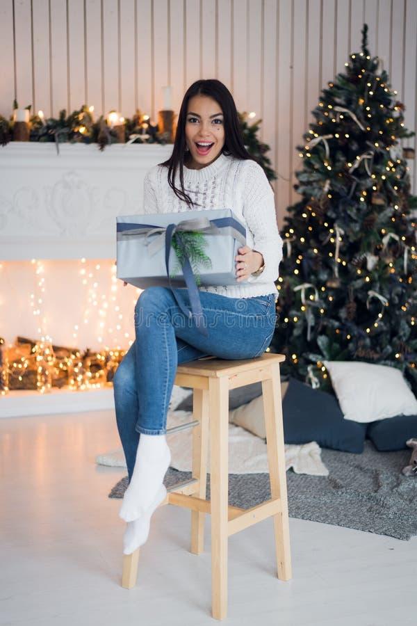 De vrolijke viering van Kerstmis Mooie verbazende jonge vrouw in jeans en witte sweatherzitting dichtbij Kerstmis royalty-vrije stock foto