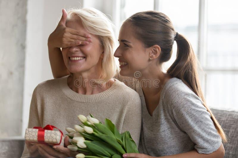 De vrolijke volwassen dochter sloot ogenmoeder alvorens een gift te geven stock foto
