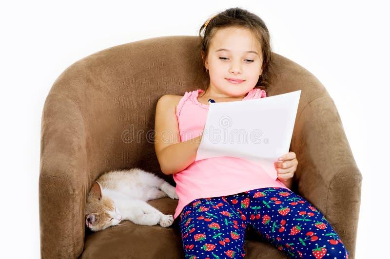 De vrolijke vrolijke spelen van het kindmeisje met een klein katje op een lichte achtergrond royalty-vrije stock afbeelding