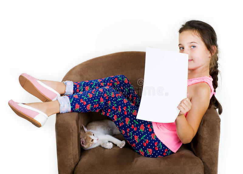De vrolijke vrolijke spelen van het kindmeisje met een klein katje op een lichte achtergrond stock foto's