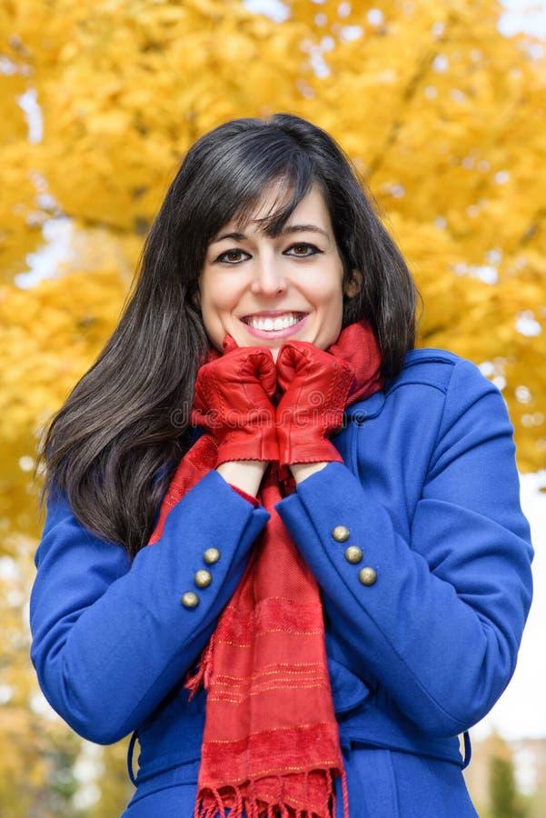 De vrolijke vrouw is koud in de herfst stock foto's