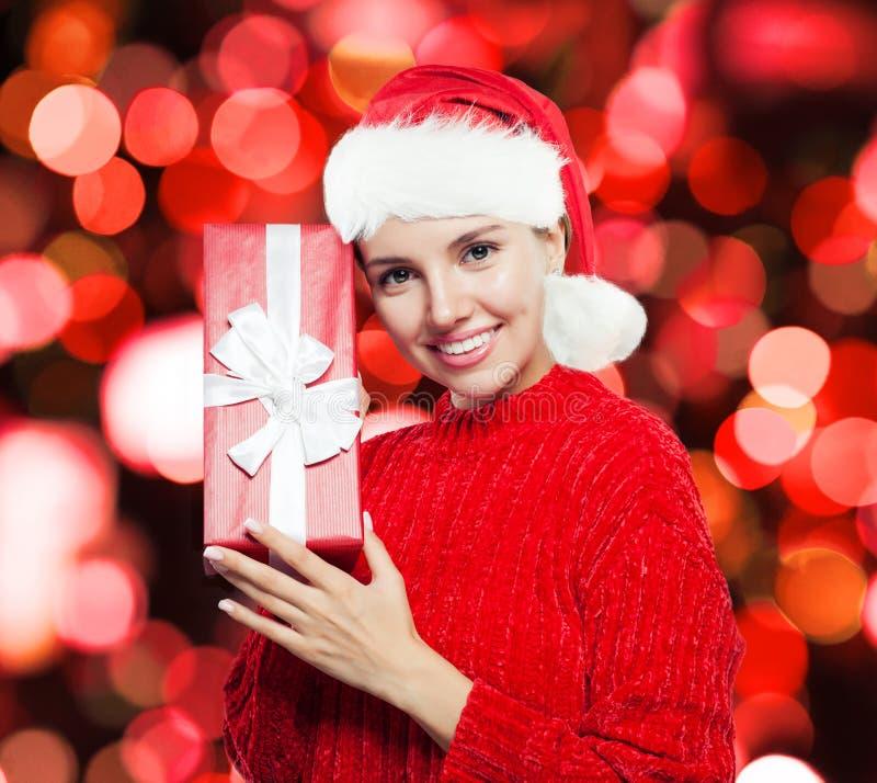 De vrolijke vrouw met rode giftdoos op partij schittert achtergrond royalty-vrije stock afbeelding