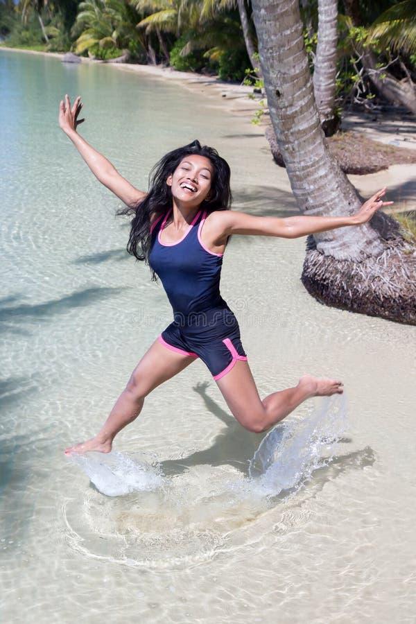 De vrolijke vrouw springt op zee royalty-vrije stock afbeelding