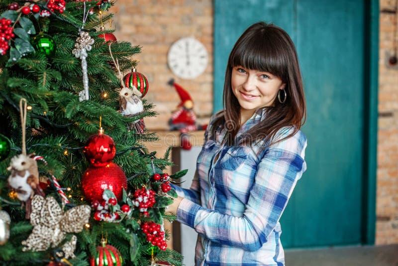 De vrolijke vrouw verfraait een Kerstboom in de ruimte Concept o royalty-vrije stock foto's