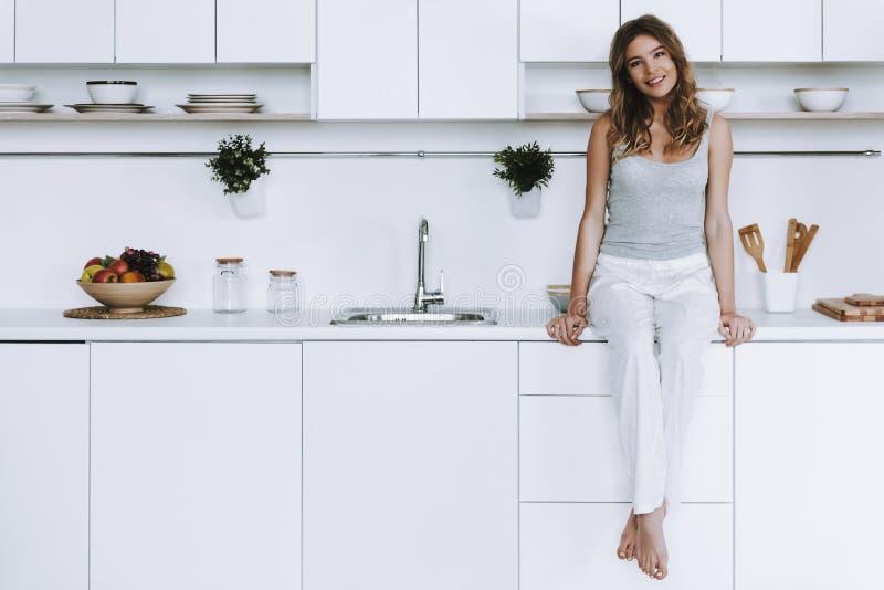 De vrolijke vrouw zit op countertop in witte moderne keuken royalty-vrije stock foto's