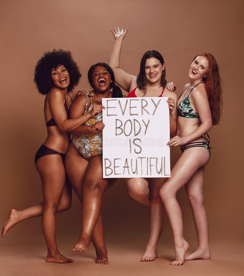 De vrolijke vrouwelijke groep met elk lichaam is mooi uithangbord stock foto's