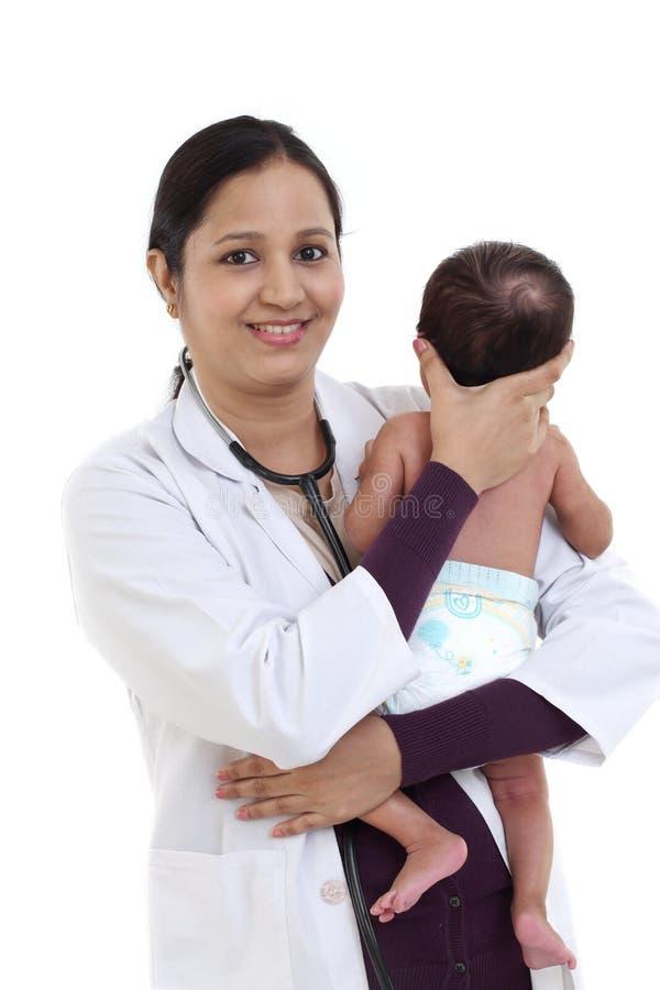 De vrolijke vrouwelijke pediater houdt pasgeboren baby stock foto's