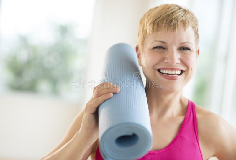 De vrolijke Vrouwenholding rolde Oefeningsmat op stock fotografie