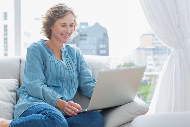 De vrolijke zitting van de blondevrouw op haar laag die laptop met behulp van royalty-vrije stock fotografie