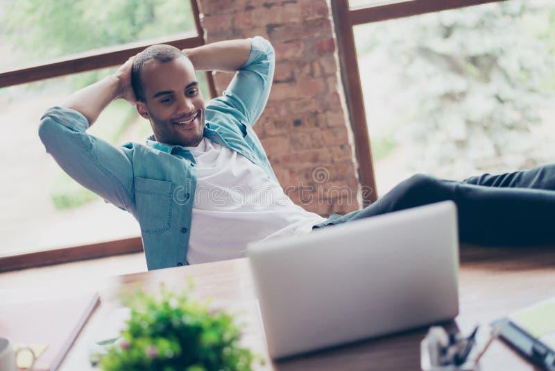 De vrolijke zwarte kerel let bij het zijn laptop scherm, op zijn het werkplaats, met wapens achter het hoofd, op het rusten, glim royalty-vrije stock foto