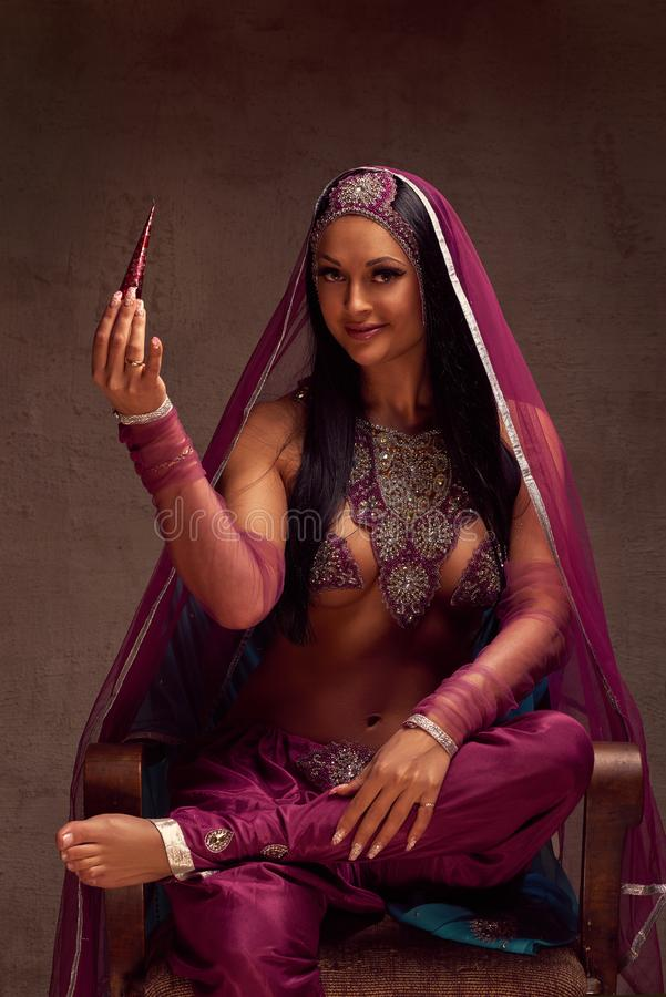 de vrouw in Afghanibroek, purdah en de versiering hebben een kegel met henna royalty-vrije stock afbeelding
