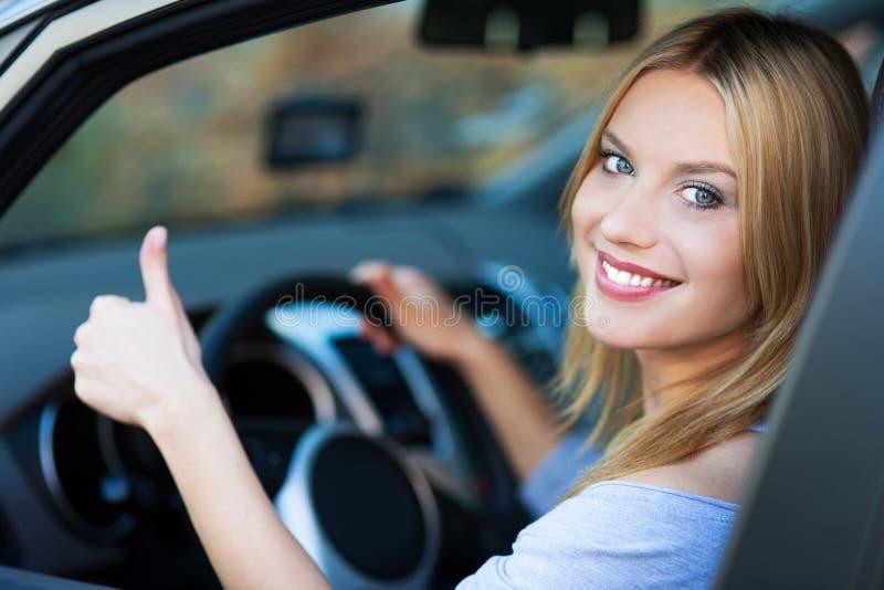 De vrouw in auto het geven beduimelt omhoog stock fotografie