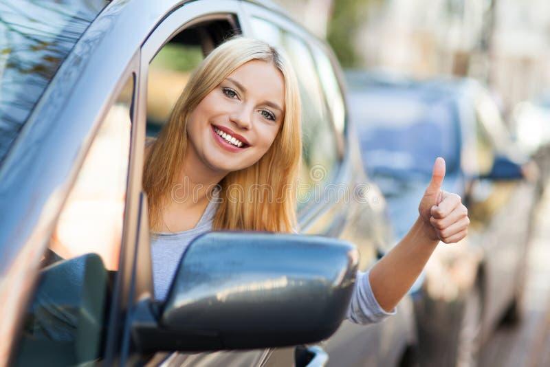 De vrouw in auto het geven beduimelt omhoog royalty-vrije stock foto's