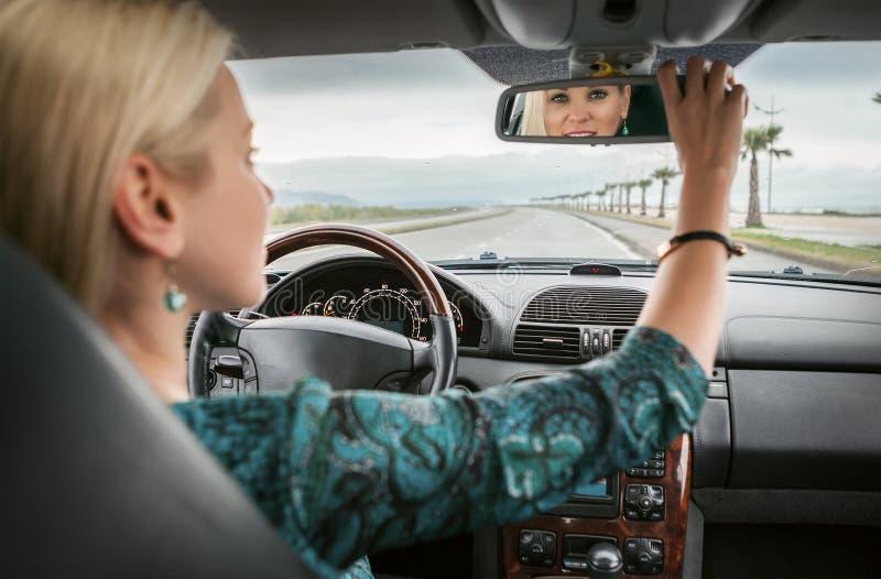 De vrouw in auto kijkt in achteruitkijkspiegel stock foto
