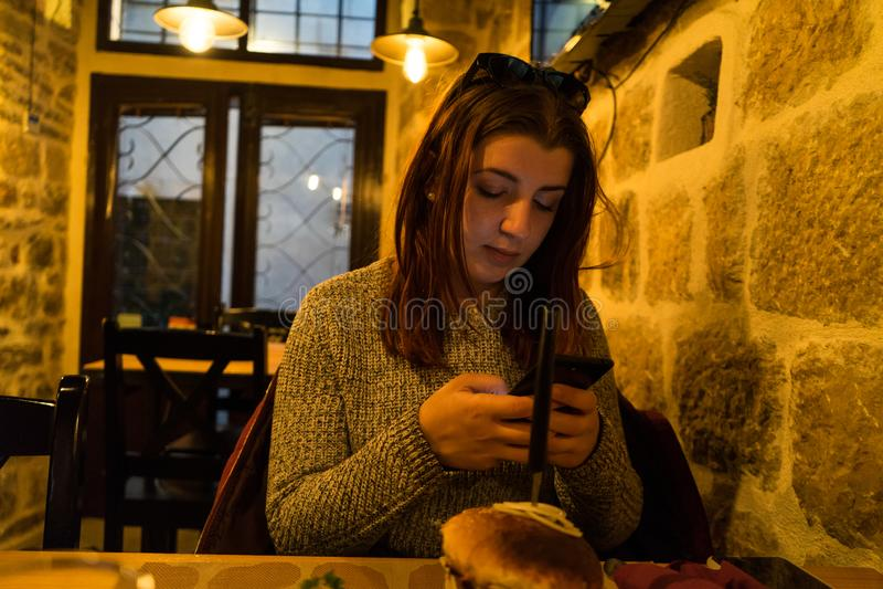 De vrouw babbelt op mobiele telefoon, terwijl in koffiebar zit Het rode hoofd jonge meisje verzendt bericht in smartphone met zon royalty-vrije stock fotografie