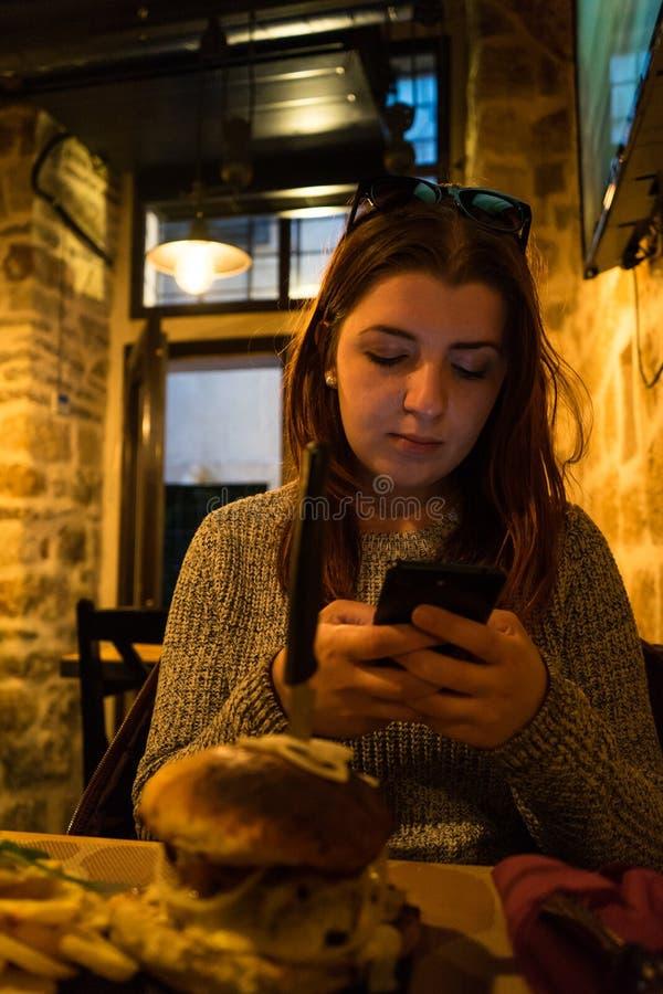 De vrouw babbelt op mobiele telefoon, terwijl in koffiebar zit Het rode hoofd jonge meisje verzendt bericht in smartphone met zon royalty-vrije stock afbeeldingen
