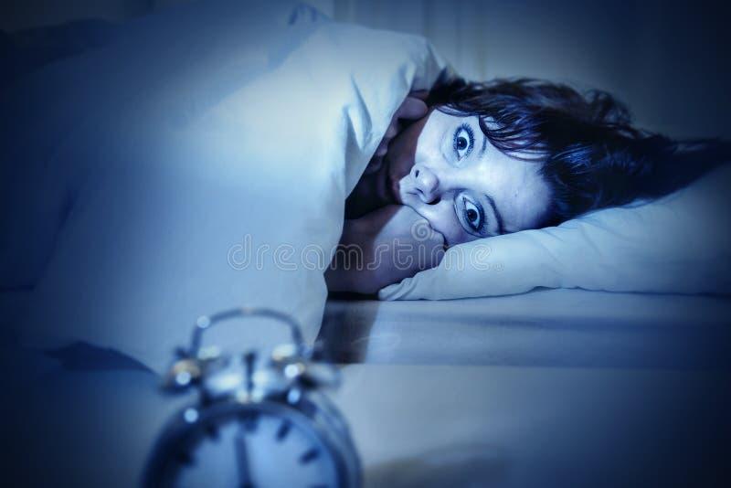 De vrouw in bed met ogen opende het lijden van slapeloosheid en slaap aan wanorde stock afbeelding