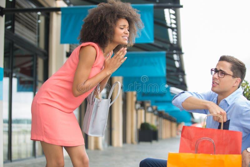 De vrouw bedelt vriend te blijven winkelend stock fotografie