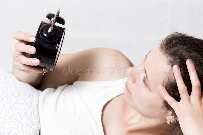 De vrouw bekijkt wekker liggend in bed in ochtend het meisje staat vroeg voor het werk op Sta op de wekker op stock afbeeldingen