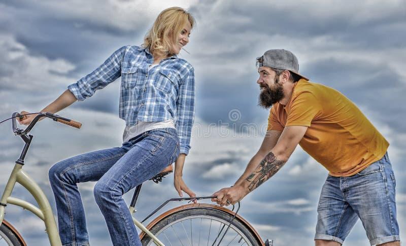 De vrouw berijdt de achtergrond van de fietshemel De dienst en hulp De mensenhulp houdt de fiets van de saldorit Meisje die terwi royalty-vrije stock fotografie