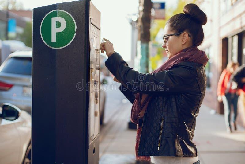 De vrouw betaalt voor parkeren stock foto's