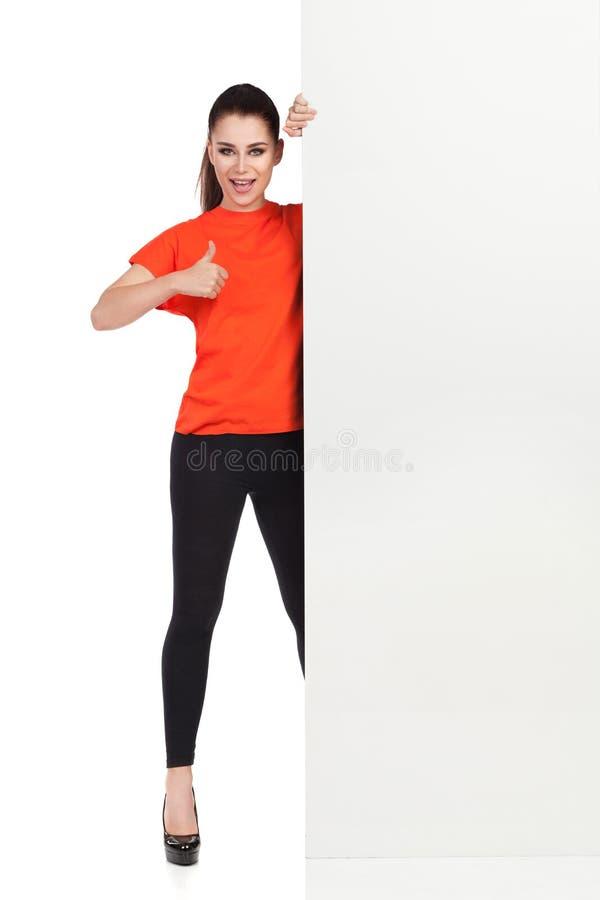 De vrouw bevindt zich achter Wit Aanplakbiljet, spreekt en toont Duim stock afbeelding