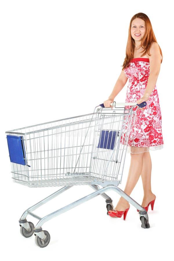 De vrouw bevindt zich met het winkelen mand royalty-vrije stock afbeeldingen