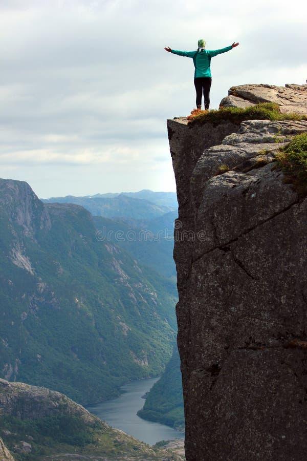De vrouw bevindt zich op een klip uitspreidend haar wapens bij Preikestolen-rots, Noorwegen stock afbeelding